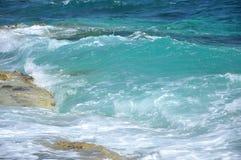 Blauwellen, die auf einer Küstenlinie zusammenstoßen Stockfoto