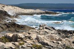 Blauwellen, die auf einer Küstenlinie zusammenstoßen Stockfotografie