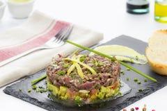 Blauwvintonijn tartare op een zwarte leiplaat met avocado Stock Foto