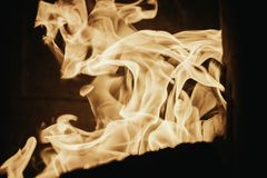 Blaze fire flame background and textured, orange and black. Flame fire texture oven blaze flaming stove coal burn fireplace grill wood climate blazing energy hot stock images