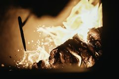 Blaze fire flame in oven, poking stick and sparks. Stove coal burn texture fireplace grill wood poker climate blazing energy hot hell inferno background fiery stock photo