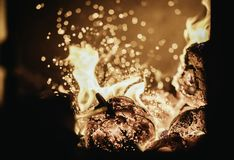 Blaze fire flame in oven, poking stick and sparks. Stove coal burn texture fireplace grill wood poker climate blazing energy hot hell inferno background fiery royalty free stock image