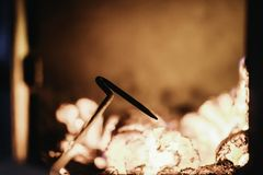 Blaze fire flame in oven, poking stick and sparks. Stove coal burn texture fireplace grill wood poker climate blazing energy hot hell inferno background fiery royalty free stock photos