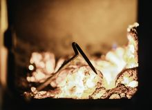 Blaze fire flame in oven, poking stick and sparks. Stove coal burn texture fireplace grill wood poker climate blazing energy hot hell inferno background fiery stock photography