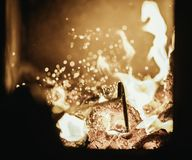 Blaze fire flame in oven, poking stick and sparks. Stove coal burn texture fireplace grill wood poker climate blazing energy hot hell inferno background fiery royalty free stock images
