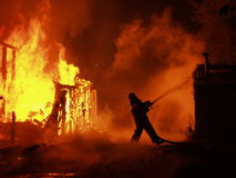 Blaze at night. Blaze at the night, burning building and fireman Stock Images