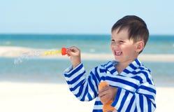 Blazende zeepbels van weinig baby de gelukkige jongen op de achtergrond van het overzees, Stock Afbeeldingen
