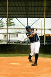 Blazing Baseball. Baseball player hits a line drive down centerfield.  Player has on uniform in navy and white Royalty Free Stock Photos