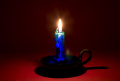 Blazing candle on red background Royalty Free Stock Image
