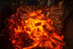 Blazing charcoal glows in the dark. Burning charcoal glows in the dark. Macro shot in detail Royalty Free Stock Image
