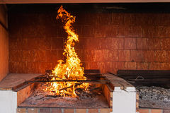 Blazing fireplace. In open traditional Spanich kitchen. Preparation for cooking classic Spanish paella royalty free stock photography