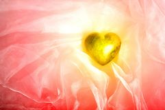 Blazing golden heart. On red textile stock image