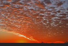 Blazing Red Sunset, Mostly Coloured Clouds with a Dark Gray Foreground. Red orange Clouds moving across the Sky at Sunset. Blazing Red Sunset, Mostly Coloured royalty free stock images