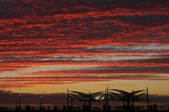 Blazing Red Sunset Sky Over the Redondo Beach Pier, Los Angeles, California. The aftermath of a passing storm made the clouds blaze red in this sunset image over Stock Photo