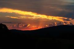 Blazing Sky sunset. With the mountains silouhette stock photos