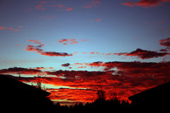 Blazing Sunset. With red cloud over house shape Stock Photography