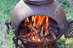 Blazing wood fire outside in a chiminea. Stock Photos