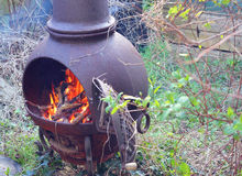 Blazing wood fire outside in a chiminea. Stock Images