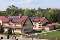 Blazkowa, Polonia - possono 10, 2018: Edificio scolastico con un campo di football americano nell'iarda Architettura del pæsaggio Fotografia Stock Libera da Diritti