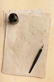 Bläckpenna, inkpot och gammalt papper Arkivfoton