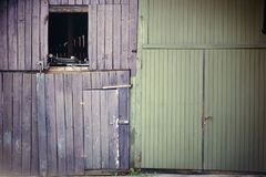 Bleached barn door. An old shaky and faded barn door with an entrance door and an open window hatch stock photo