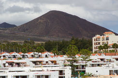 The bleak volcanic mountains and hills overlooking Playa Las Americas and Los Christianos in Teneriffe in the Canary Islands on a Stock Image