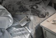 Blechdosetelefon auf Bett Stockbild
