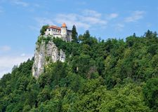 Bled castle enthroned on a rock. Surrounded by trees Stock Photo