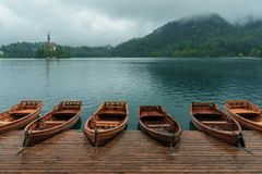 Bled with lake, island, castle, boats and mountains in background in misty and rainy day, Slovenia. Europe stock image