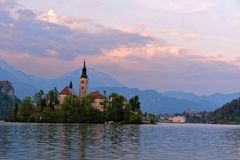 Little Island with Catholic Church in Bled Lake, Slovenia. Bled with lake, island, castle and mountains in background royalty free stock images