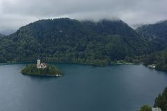 Bled with lake, island, castle and mountains in background in misty and rainy day. Slovenia, Europe stock photography
