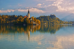 Bled lake and pilgrimage church with autumn mountain landscape background stock images