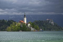 Bled lake and pilgrimage church in sunlit with dark background Royalty Free Stock Images
