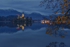 Bled lake and pilgrimage church at twilight reflected in water. Island on Bled lake and pilgrimage church of the Assumption of Mary reflected in water with stock photo