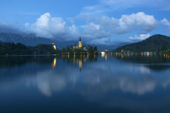 Bled lake and pilgrimage church at twilight reflected in water Stock Images