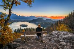 Bled, Slovenia - Red hair runner woman relaxing and enjoying the beautiful autumn view and the colorful sunrise of Lake Bled Royalty Free Stock Photo