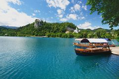 Bled, Slovenia. Tourists on large pletna boat sightseeing on Lake Bled with castle in the background Stock Photography