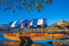 Bled, Slovenia - Traditional blue Pletna boat in the autumn sunshine at Lake Bled. With Bled Castle at background Royalty Free Stock Photos