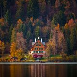 Bled, Slovenia - Typical Slovenian alpen house by the Lake Bled with boats and beautiful colorful autumn forest. At sunset royalty free stock photos