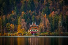 Bled, Slovenia - Typical Slovenian alpen house by the Lake Bled with boats and beautiful colorful autumn forest. At sunset royalty free stock image