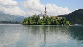 Famous landmark. Island in Lake Bled with church in the Julian Alps, Slovenia. Bled in spring, popular tourist and travel destinat stock video footage