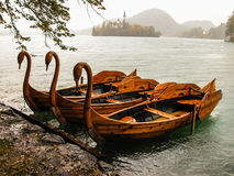 Bled swan boats. Wooden Bled swan boats and Bled island church at background Royalty Free Stock Images