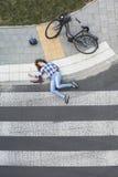 Bleeding car crash victim next to bike Royalty Free Stock Photo