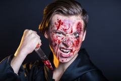 Bleeding face. Man with bleeding face. Professional make up for horror film (makeup faceart bodyart), cosmetics. Realistic photo. Can be used for Halloween party Royalty Free Stock Photos