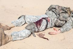 Bleeding. Injured airborne infantry paratrooper shot in leg hip on desert sand. Blood spilled but tourniquet is on, he will be alive Stock Image