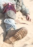 Bleeding. Injured airborne infantry paratrooper shot in leg hip on desert sand. Blood spilled but tourniquet is on, he will be alive Stock Photos