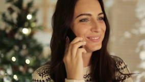 Bleiben angeschlossen Schöne junge lächelnde Frau in der weißen Strickjacke sprechend am Handy mit defocused Weihnachten stock video footage