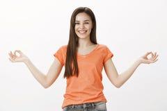 Bleiben positiv und ruhig in der städtischen Hölle Positive frohe kaukasische Studentin im orange T-Shirt, verbreitete Hände mit stockfotografie