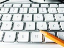 Bleistift über einer weißen Computertastatur Stockbilder