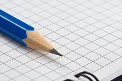 Bleistift auf überprüftem Notizbuch Lizenzfreies Stockfoto